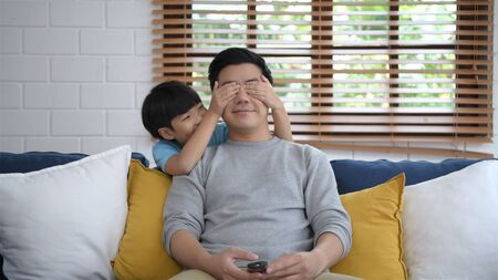 Family concept. The son is making his father freak in the living room. 4k Resolution.