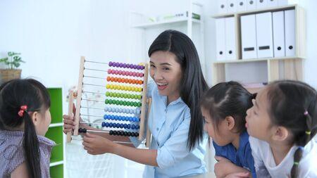 Concepts pédagogiques. L'enseignant enseigne les mathématiques avec un boulier pour les enfants de la maternelle en classe, avec un visage souriant brillant. Banque d'images