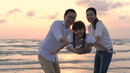 Family concept. Parents swinging daughter up into air on the beach. Stockfoto