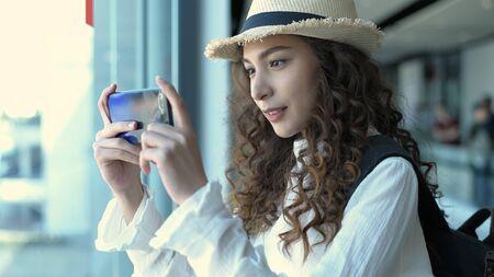 Travel concept. Beautiful girl taking photo outside the passenger terminal. 4k Resolution. Stockfoto