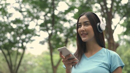 Holiday concept. The girl is listening to the music in the park. 4k Resolution.