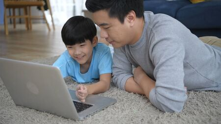 Family concept. Parents play notebook with son in the house. 4k Resolution. Stockfoto