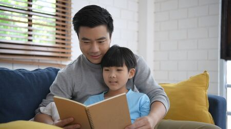 Family concept. Father teaching his son to read a book in the house. 4k Resolution.