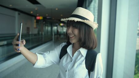Tourism concept. An Asian woman is taking a photo inside the airport. 4k Resolution.