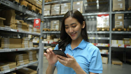 Business concepts. An Asian woman is checking products in a warehouse with an application from a mobile phone. 4k Resolution. Stockfoto - 152832911