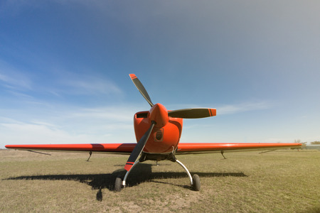 airplane ultralight: Red sport aircraft at the airport on a sunny day.
