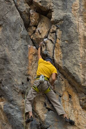 lead rope: Young male climber hanging on a cliff with a rope.