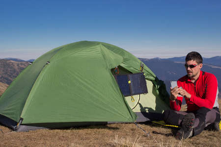panel: The guy in the mountains, hike with a backpack, and a solar panel for charging accumulators.
