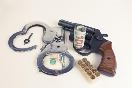 malandros: D�lares esposas arma de mano cartuchos sobre un fondo blanco. Foto de archivo