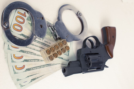 malandros: Dollars handcuffs handgun cartridges on a white background.