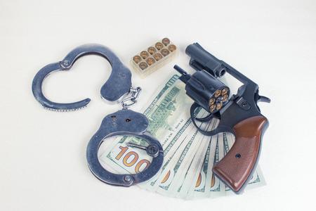 malandros: Dollars handcuffs handgun cartridges on a white background.