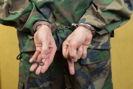 shackled: Young man in handcuffs wearing camouflage uniforms in the room.