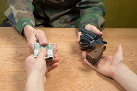 transfers: Transfers of money in exchange for a gun under certain conditions, sitting at the table.