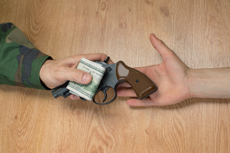 landmine: Transfers of money in exchange for a gun under certain conditions, sitting at the table.