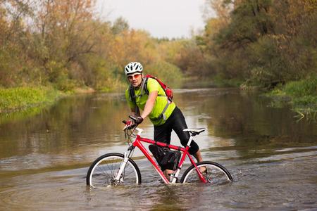 Homme cycliste voyageant avec vélo et sac à dos. Banque d'images
