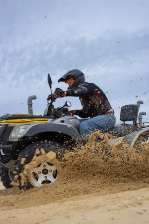 quad: The race in difficult conditions on the sand on a quad bike.