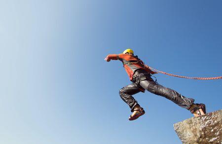 saltar la cuerda: El hombre que salta de un acantilado con una cuerda en un día soleado.