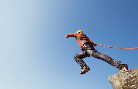 Man jumping off a cliff with a rope on a sunny day. Stock Photo