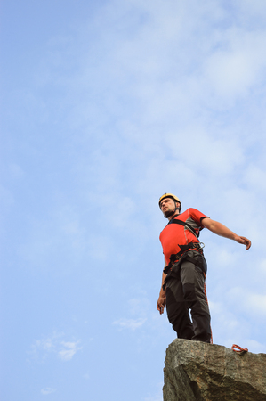 cliff jumping: Man jumping off a cliff with a rope on a sunny day. Stock Photo