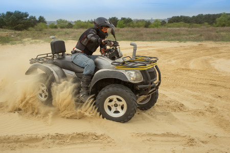 powerfull: Racing ATV in sand.