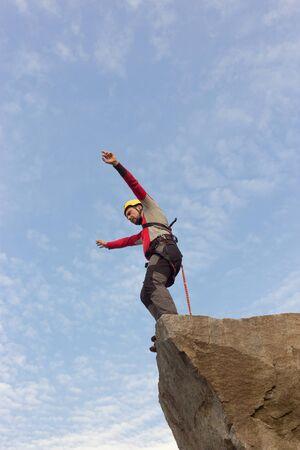 bungee jumping: El hombre que salta de un acantilado con una cuerda en un día soleado.