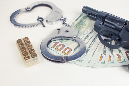 malandros: Pistol, handcuffs ammo and money on a white background. Foto de archivo