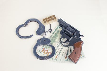 malandros: Pistola, munici�n manillas y dinero en un fondo blanco.