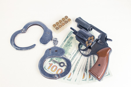 Pistol, handcuffs ammo and money on a white background. Stock Photo