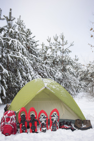 Camping in the winter campaign of winter with snowshoes and tent.