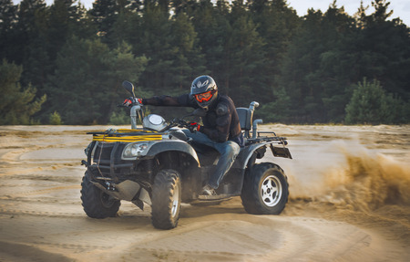 powerfull: Racing ATV in the sand in the summer.