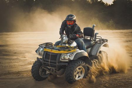 Racing ATV in het zand in de zomer. Stockfoto