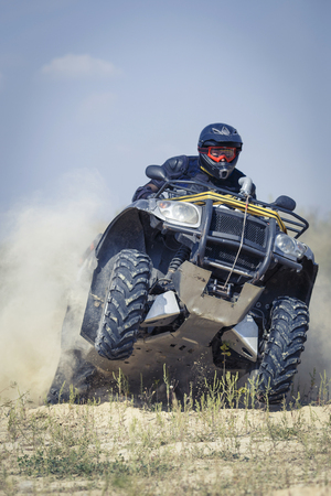 protective clothing: A man riding ATV in sand in protective clothing and a helmet.