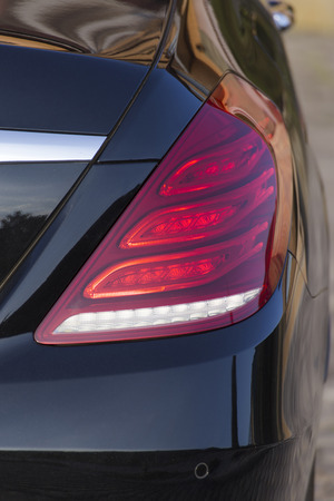 taillight: Rear red stop signal lamp on a modern black car.