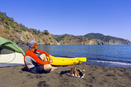 A man traveling by canoe along the coast in the summer. Stock Photo