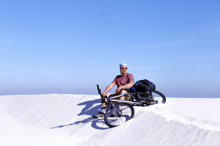 Travel by bike in the desert with a backpack and tent. Stock Photo