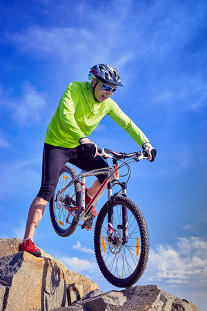 researching: Cyclist in helmet with mountain bike in the mountains. Stock Photo