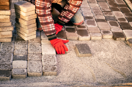 Construction of a sidewalk of blocks of workers in the summer. Stock Photo