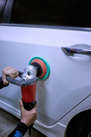 cleaning service: Polishing of the white car with the help of power tools on the service. Stock Photo