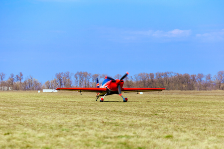 A sport aircraft on a dirt road on a sunny day.