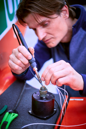 shrinkage: The electrician performs the soldering of wires with a soldering iron. Stock Photo