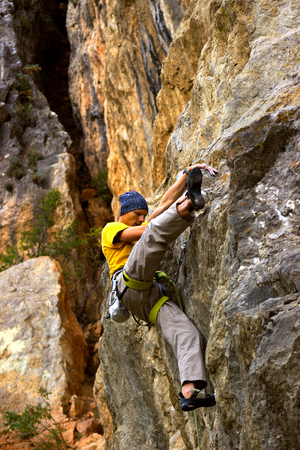 Young male climber hanging on a cliff with a rope.