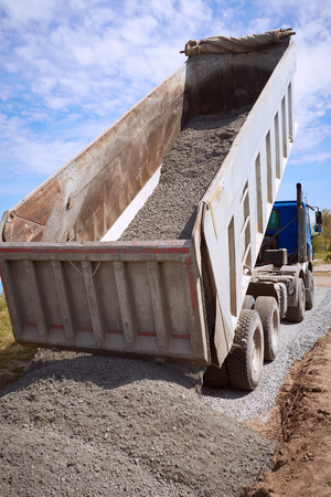 Dumper truck for unloading rubble on the road construction site. Stock Photo - 78896671