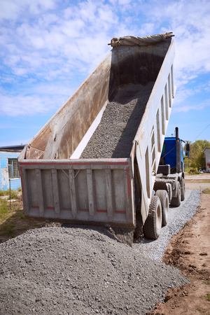 Dumper truck for unloading rubble on the road construction site. Stock Photo - 81488386