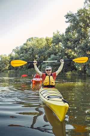 Mens die in een kajak op rivier paddelen. Stockfoto - 83469226