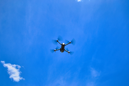 A small gray quadrocopter against the blue sky. Stock Photo