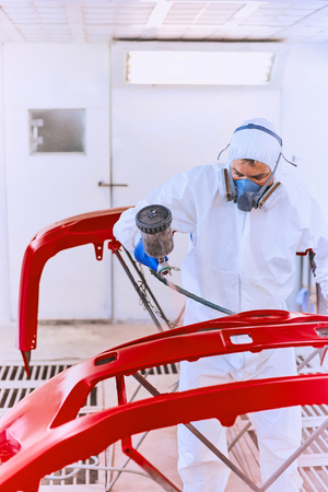 Painting the cars bumper red on the service.