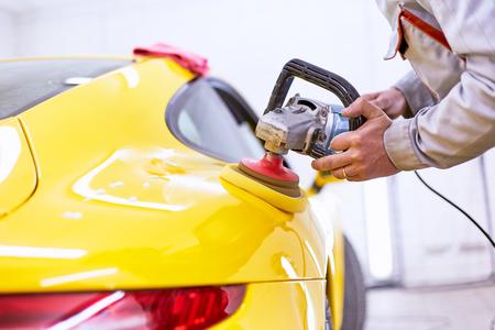 Polishing the yellow machine for customer service. 스톡 콘텐츠
