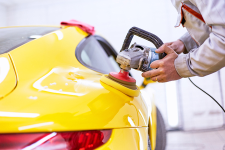 Polishing the yellow machine for customer service. Standard-Bild