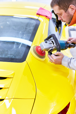 Polishing the yellow machine for customer service. 스톡 콘텐츠