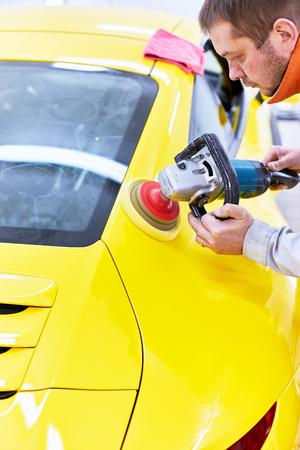 Polishing the yellow machine for customer service. Archivio Fotografico